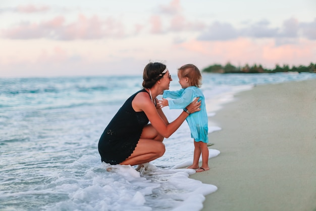 Beautiful mother and daughter at caribbean beach enjoying summer vacation.