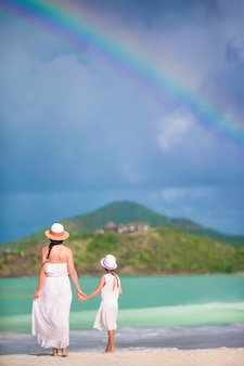 Beautiful mother and daughter on caribbean beach with amazing rainbow