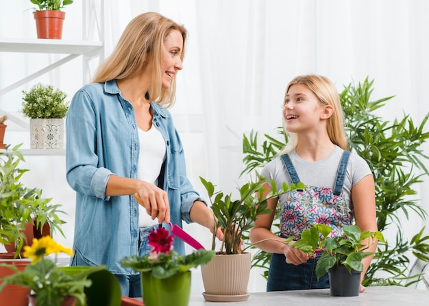 Beautiful mother and daughter in greenhouse