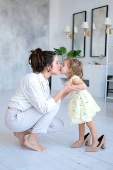 Beautiful mother and daughter hugging and kissing in a bright and spacious apartment.