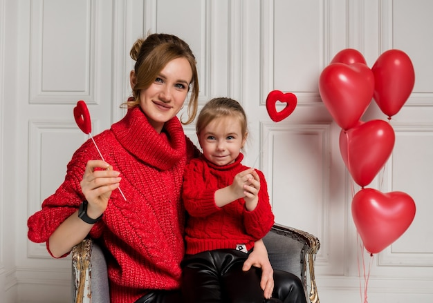 Beautiful mother and daughter sitting in a chair and holding hearts on a stick on a white background with red balloons
