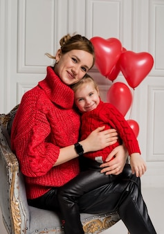 Beautiful mother and daughter sitting and hugging in a chair on a white background with red balloons