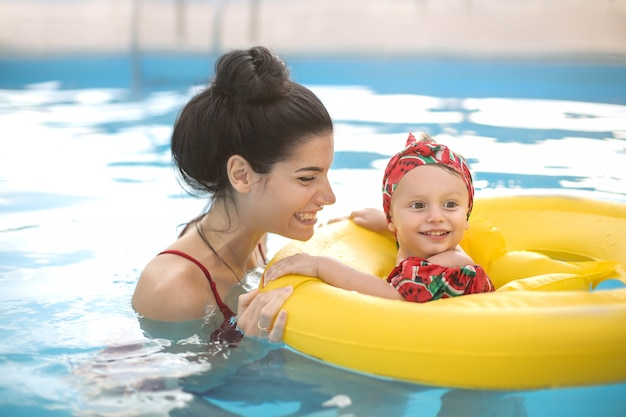 Beautiful mother and daughter swimming in a swimming pool