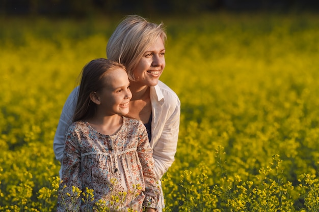 Beautiful mother and daughter on a yellow rape field