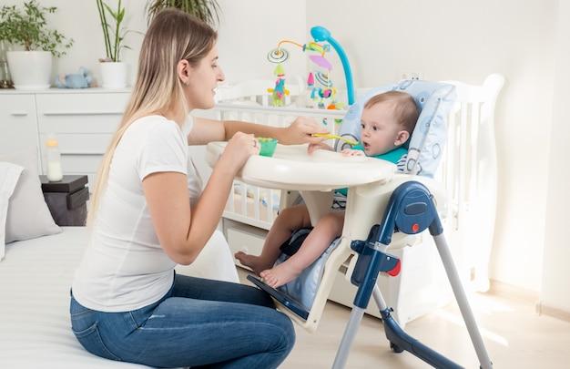거실에서 유아용 의자에 아기를 먹이 아름다운 어머니