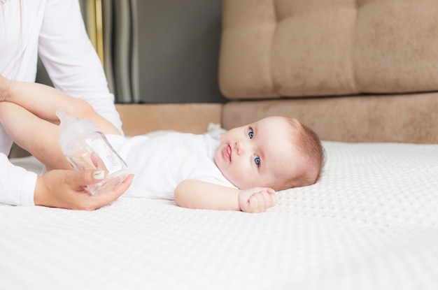 美しい母親が自宅の牛乳瓶から女の赤ちゃんに餌をやる。
