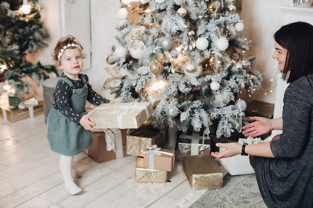 Beautiful mother gives a gift to her daughter at home