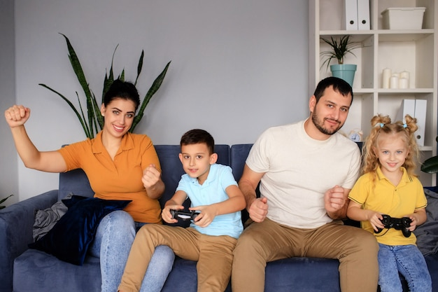 Beautiful mother and handsome father with their daughter and son spending time together at home and playing video games. happy family concept.