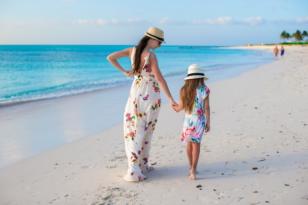 Beautiful mother and her adorable little daughter enjoy summer vacation