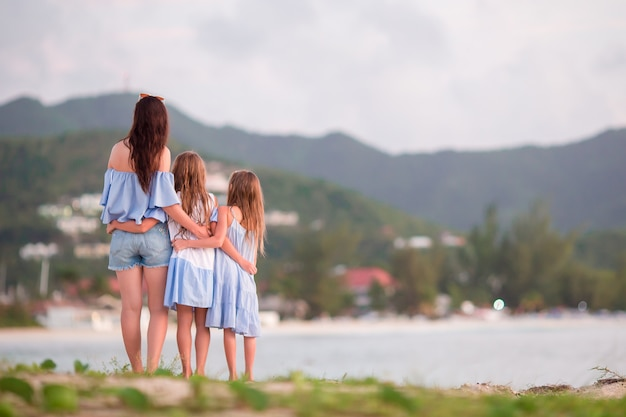 Beautiful mother and her adorable little daughters on the beach