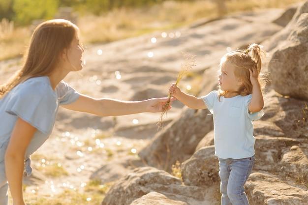 Bella madre e sua figlia carina dai capelli lunghi stanno camminando sul prato di pietra