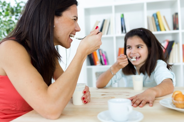 Beautiful mother and her daughter eating iogurt at home.