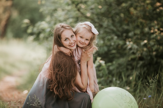 Beautiful mother and her little daughter outdoors. nature. beauty mum and her child playing in park together. outdoor portrait of happy family. happy mother's day joy. mom and baby