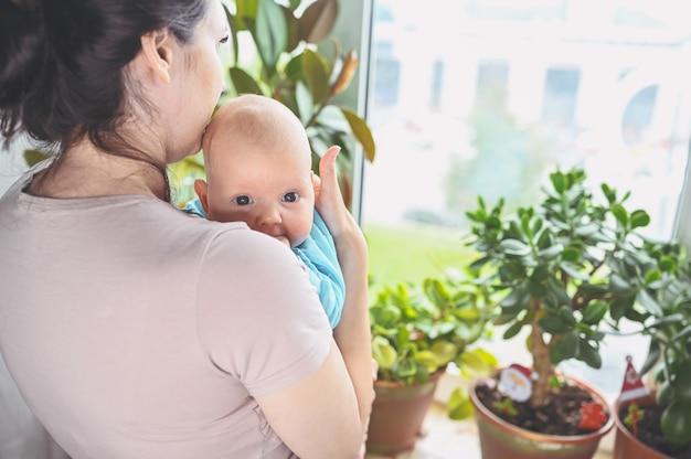 Красивая мать держит на руках своего маленького симпатичного новорожденного сына