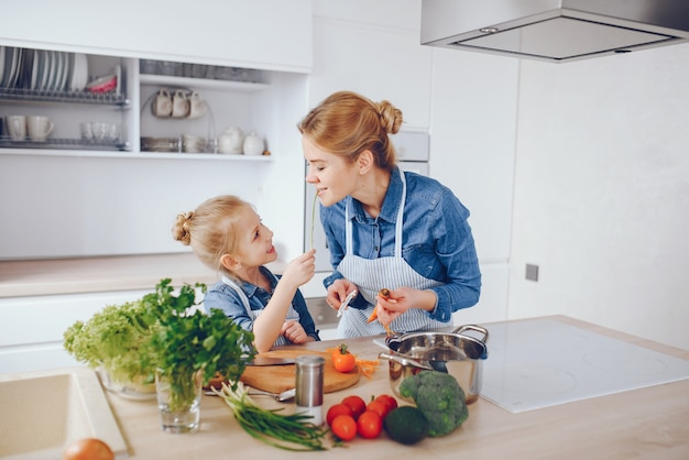 파란색 셔츠와 앞치마에 아름다운 어머니는 집에서 신선한 야채 샐러드를 준비하고있다