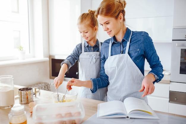Красивая мать в синей рубашке и фартуке готовит обед у себя дома на кухне