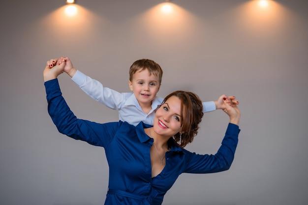 ドレスを着た美しい母親が息子を背負っている