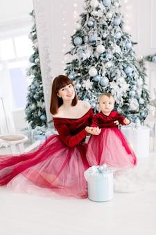 아늑한 조명 장식 스튜디오에서 그녀의 귀여운 아기 소녀와 함께 포즈를 취하는 빨간 드레스에 아름다운 어머니