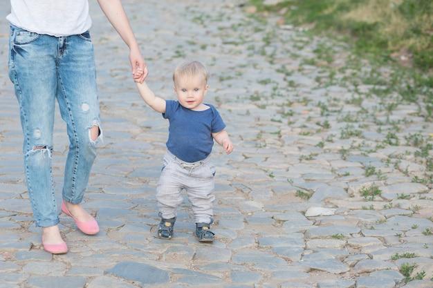 美しい母親は、最初のステップで彼女の小さな男の子と一緒に古い道を歩いています