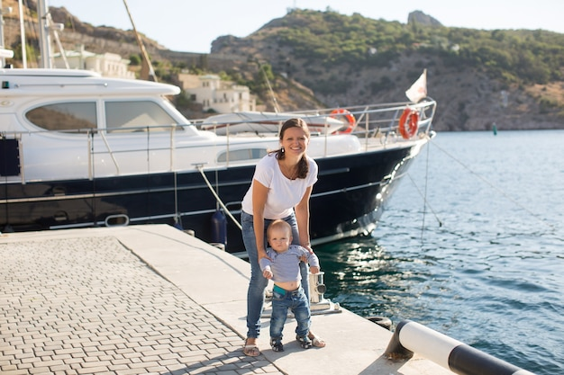 美しい母親は、最初のステップで彼女の小さな男の子の息子と一緒に桟橋を歩いています