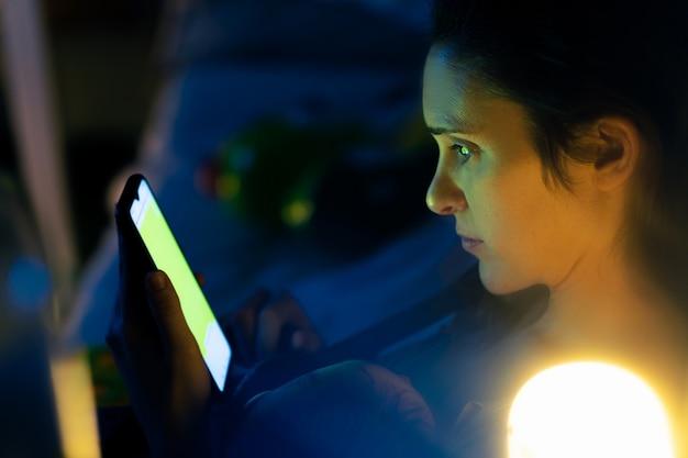 彼女の胸の読書で彼の赤ちゃんと一緒に夜ソファに座ってスマートフォンを見ている美しい母親