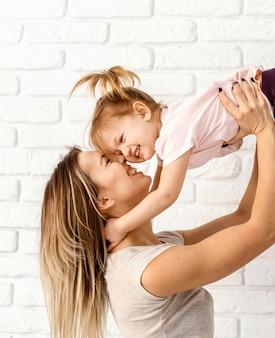집에서 그녀의 딸과 함께 노는 아름 다운 어머니