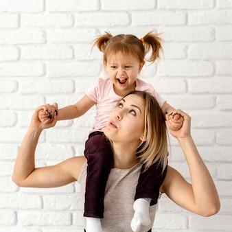 家で娘と遊ぶ美しい母親