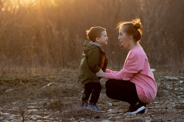 Beautiful mother playing with her son in nature against sunset. mother's day concept.