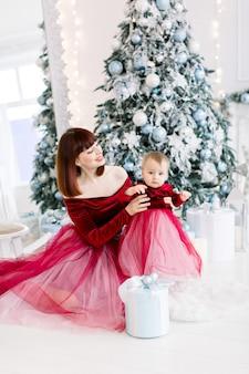 아늑한 조명 장식 스튜디오에서 그녀의 귀여운 아기 소녀와 함께 포즈를 취하는 아름다운 어머니