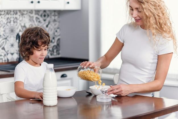 美しい母親は、コーンフレークとミルクから健康的な朝食を彼女の最愛の息子のために準備します。
