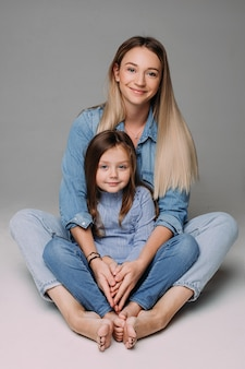 아름다운 어머니는 예쁜 딸과 함께 앉아 미소를 짓고 있다