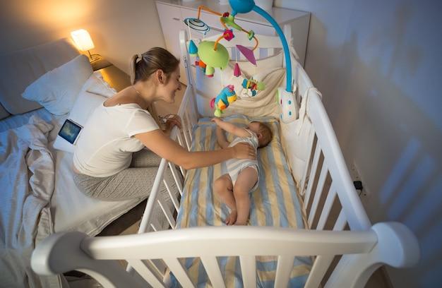 아기 침대 옆에 앉아 아기를 바라보는 아름다운 어머니