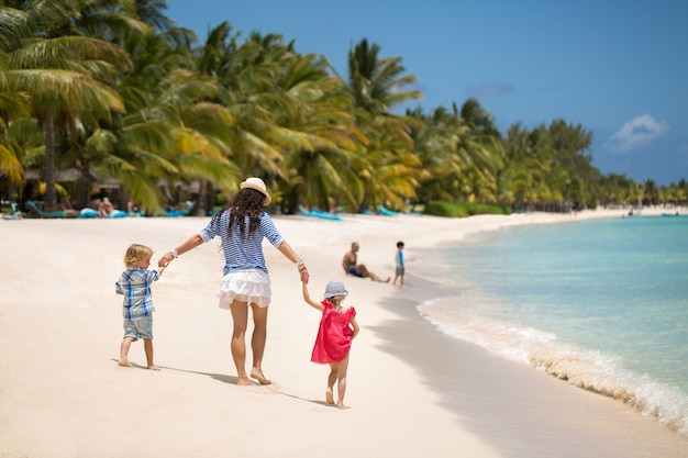 Beautiful mother, son and daughter walking on the beach of the indian ocean.