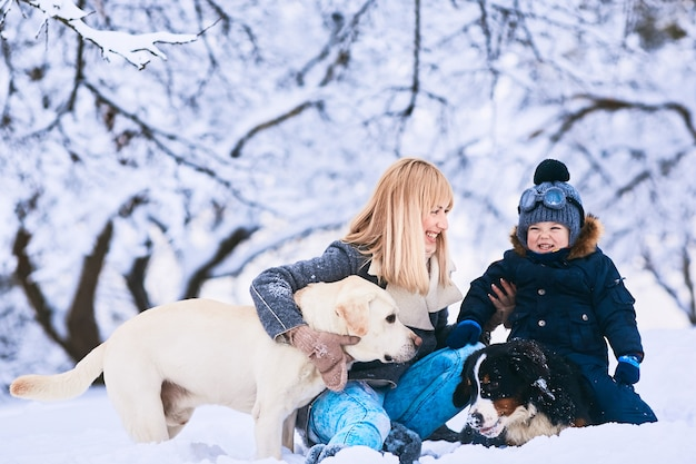 The beautiful mother, son and dogs sitting on the snow