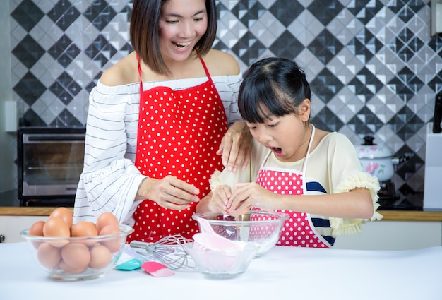 Beautiful mother teaches daughter prepare dough in the kitchen.concept family happy.