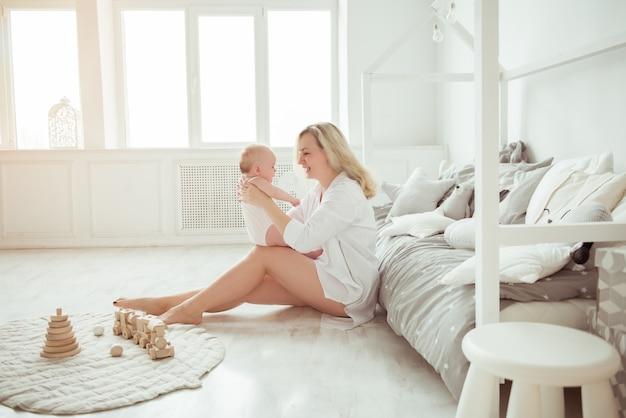Красивая мама с милым малышом, обнимающимся в спальне