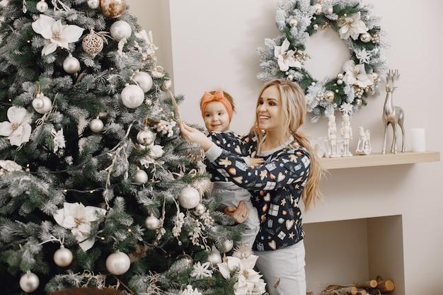 子供を持つ美しい母親。クリスマスの雰囲気の中で家族。クリスマスツリーを着ている人。