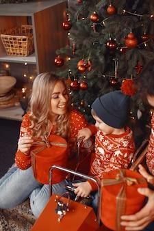 子供を持つ美しい母親。クリスマスプレゼントのある家族。