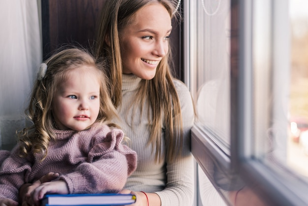 Beautiful mother with daughter. family sitting in the room near window looking outside