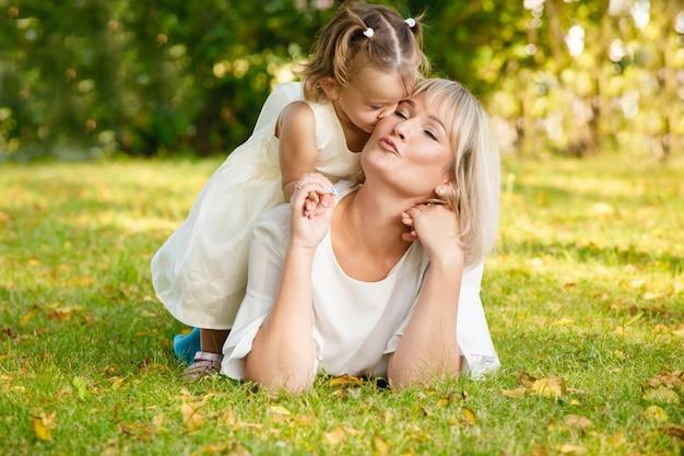 公園で夏の屋外で薄着の娘と美しい母親