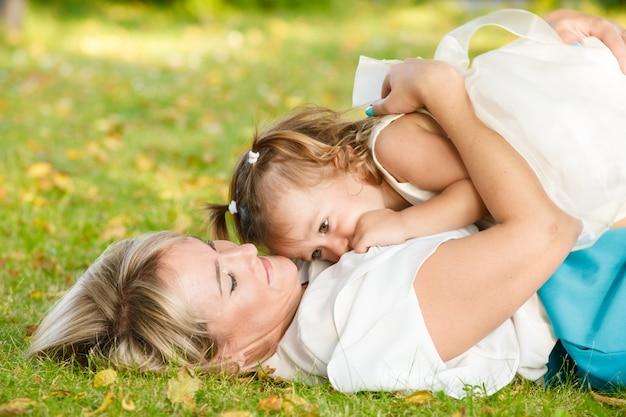 公園で夏に屋外で娘と美しい母親