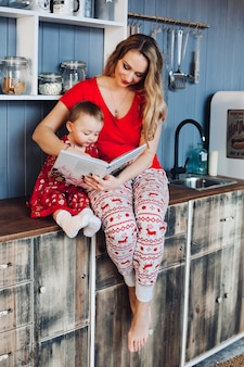 Beautiful mother with little daughter in christmas pajamas reading book at kitchen.