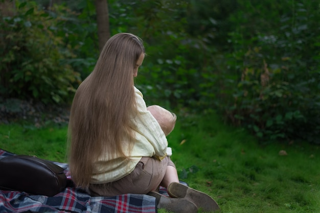 Beautiful mother with long hair breastfeeds her baby .back view