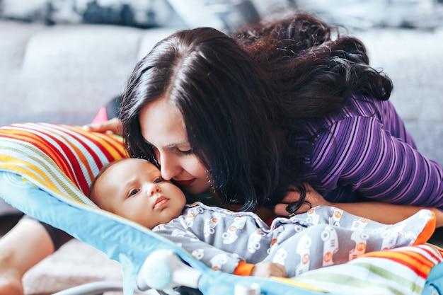 집에서 갓 태어난 귀여운 아기와 함께 아름 다운 어머니