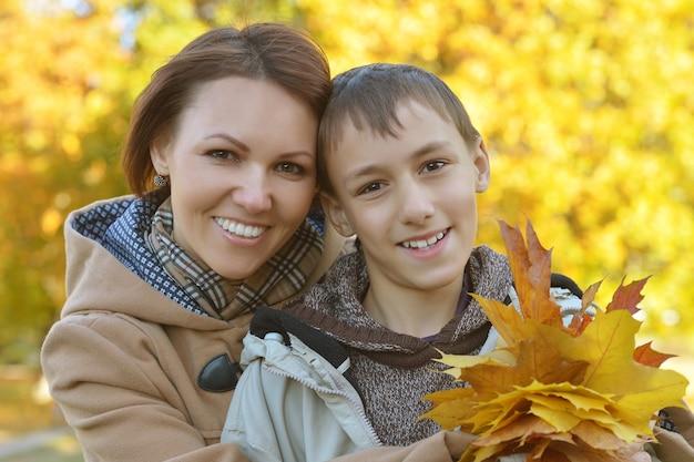 秋の公園で息子と美しい母親