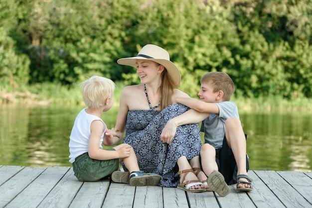 2人の幼い息子を持つ美しい母親が川岸の桟橋に座っています。