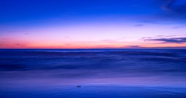 아름다운 동작은 열대 푸켓 섬의 잔잔한 바다 위에 극적인 하늘 구름과 함께 긴 노출 일몰 또는 일출을 흐리게 합니다. 놀라운 자연 전망과 자연 바다의 빛입니다.