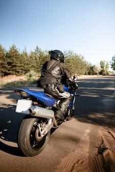 林道を走る美しいバイク。夕日の暖かい太陽光線の中でバイクに乗って空の道を運転して楽しんでください。