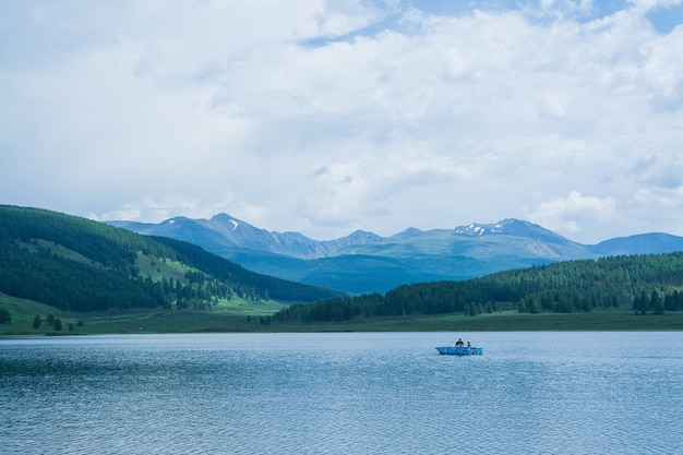 A beautiful mountain lake with reeds surrounded by mountain ranges and impenetrable forests.  fishing boat on the lake.