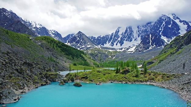 Красивое горное озеро с бирюзовой прозрачной водой на алтае. высокие горы со снегом и деревьями